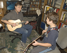 Photo of a guitar student and instructor.